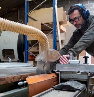 travail bois massif atelier machine découpe artisan menuisier mur briques